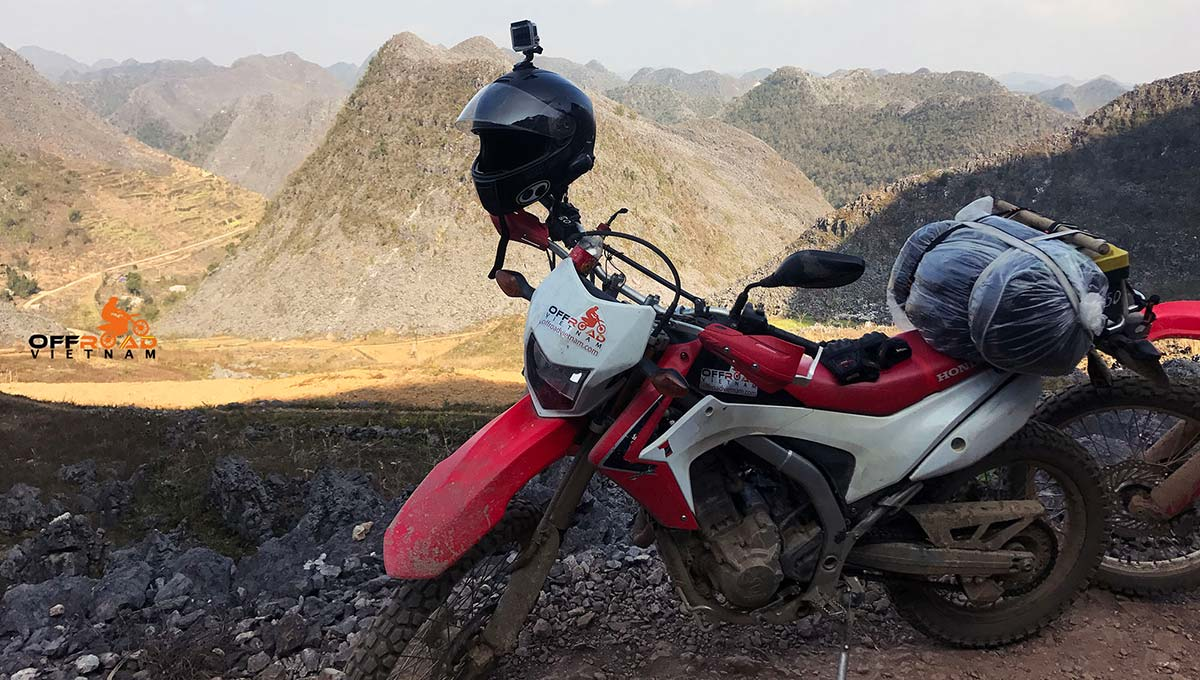 Offroad Vietnam Dirt Bike Rental - 2014-2017 Honda dirt (trail) bike Honda CRF250L 250cc Red & White, front disc brake, back drum brake with rear luggage rack on a Ha Giang motorbike tour. Luggage loaded.